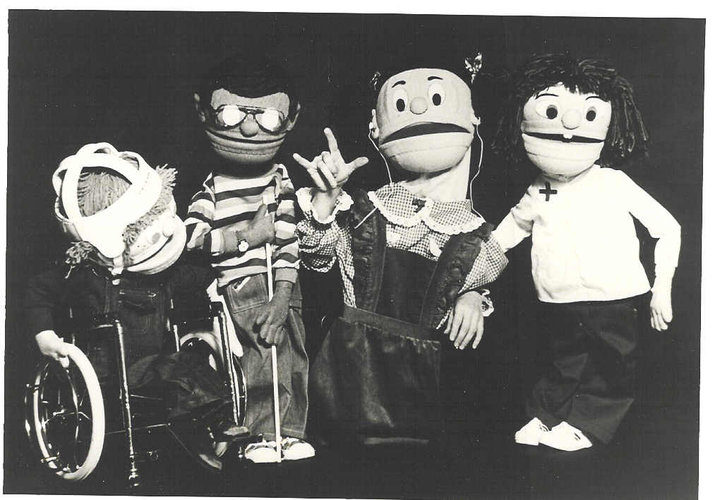 4 puppets are pictured, Mark who has CP and uses a wheelchair, Reanaldo who has a visual impairment, Many who has a hearing impairment and is making the sign for I Love You and Ellen Jane who has Down syndrome.