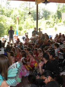 Photo of a large group of children watching the puppet show, some wearing butterfly wings