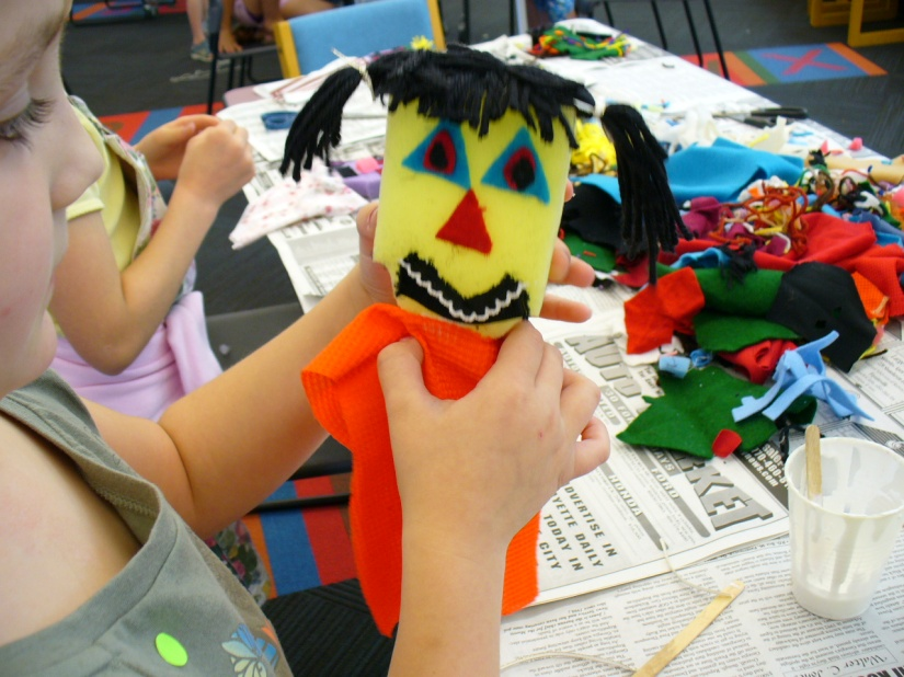 A girl holding a bright foam-and-cloth puppet with black yarn pigtails