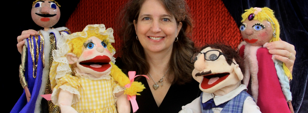 Director Nancy Riggs surrounded by puppets