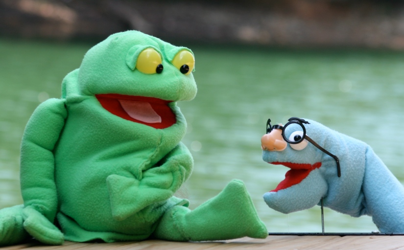 Big green Tiddalick the Frog hand a rod puppet and blue Eel rod puppet posing in front of a lake