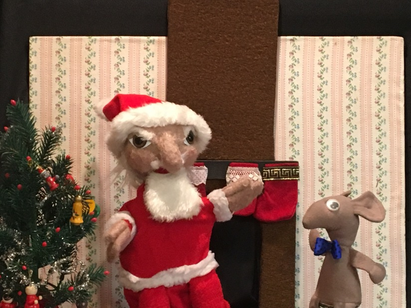 The Santa puppet is pictured with the Mouse, the Christmas tree, and the stockings hung with care by the fireplace