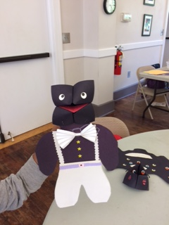 Paper person puppet with a tuxedo made from construction paper, including a bow tie from folded paper