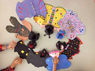 A circle of paper puppet bats and butterflies decorated with markers and stickers