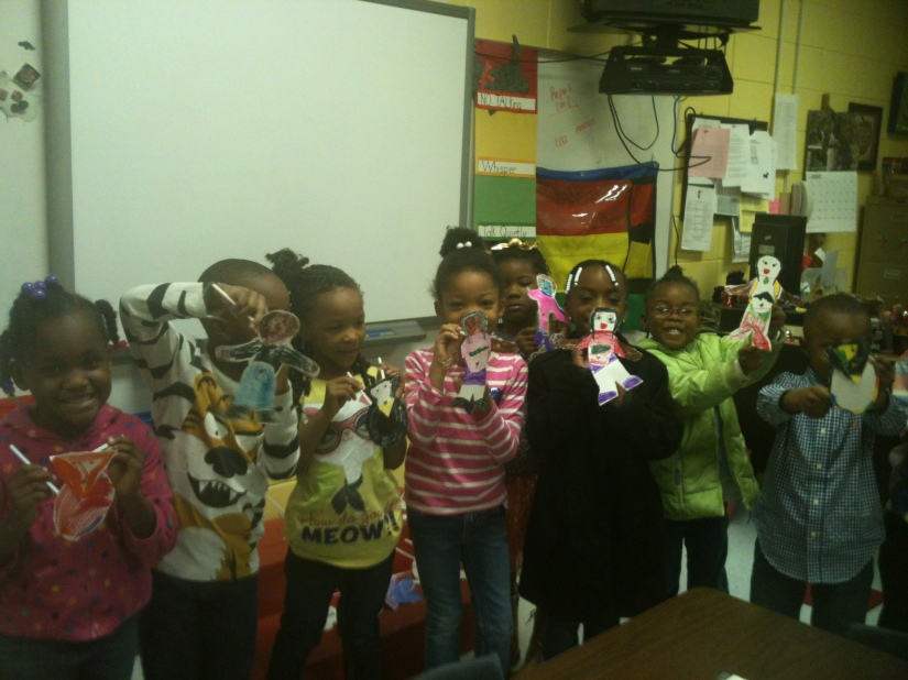 A group of Kindergarten students holing shadow puppets they made in a workshop