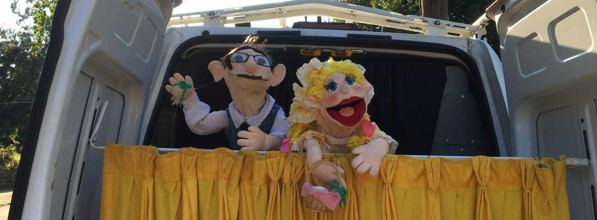 Two puppets peek over the curtain stretched across the open back doors of the van