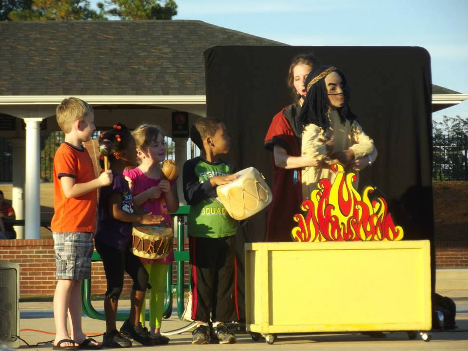children with instruments on stage with the puppeteer and Chief Gray Eagle puppet