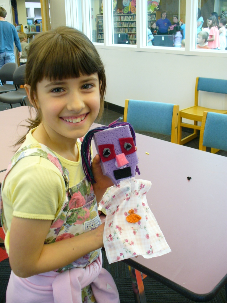 A girl holding a puppet with a purple sponge head and flowered cloth body