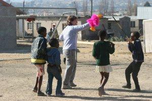 Puppeteer manipulates a bright pink bird puppet for several African children