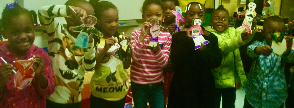 Kindergarten students holding shadow puppets they made from cardstock