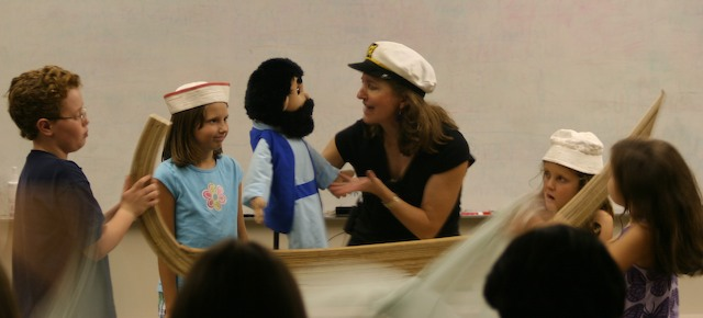 Photo showing the puppeteer with the Jonah puppet and children holding the boat and wearing sailor hats