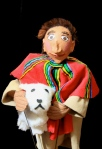 The Joseph rod puppet wearing a bright re coat with colorful stripes and his sheep