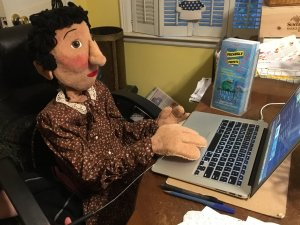 Woman Puppet with dark hair, light skin sitting at desk typing on a laptop