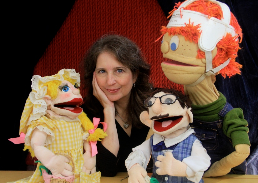 Director Nancy Riggs surrounded by 3 puppets